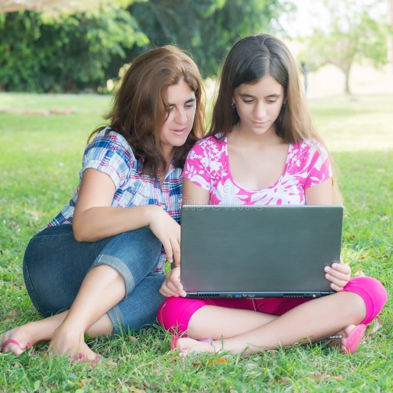Muchacha hispánica y su madre que usa un ordenador portátil al aire libre fotografía de archivo libre de regalías