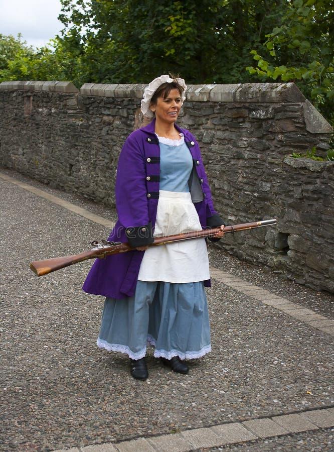 Muchacha histórica en un traje con un mosquete en las paredes de Londonderry fotos de archivo
