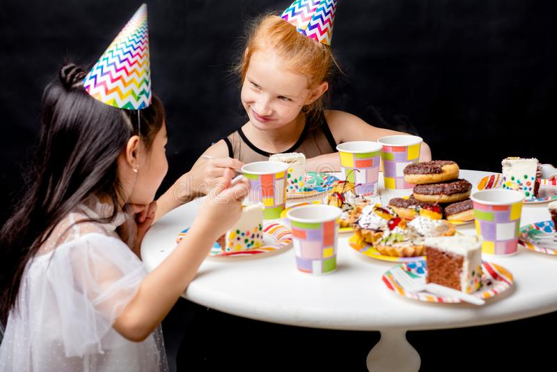 Muchacha impresionante dos que habla mientras que come la torta de cumpleaños imagen de archivo