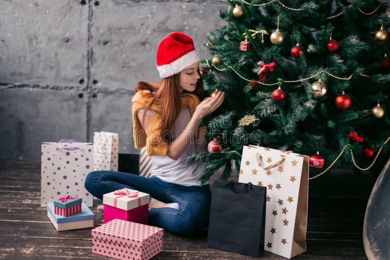 Muchacha impresionante que sostiene una bola de la Navidad en su mano imagen de archivo libre de regalías