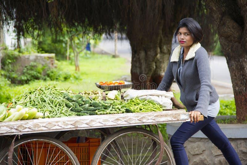 Muchacha india joven con el pelo corto que vende verduras en un carro, Pune fotografía de archivo