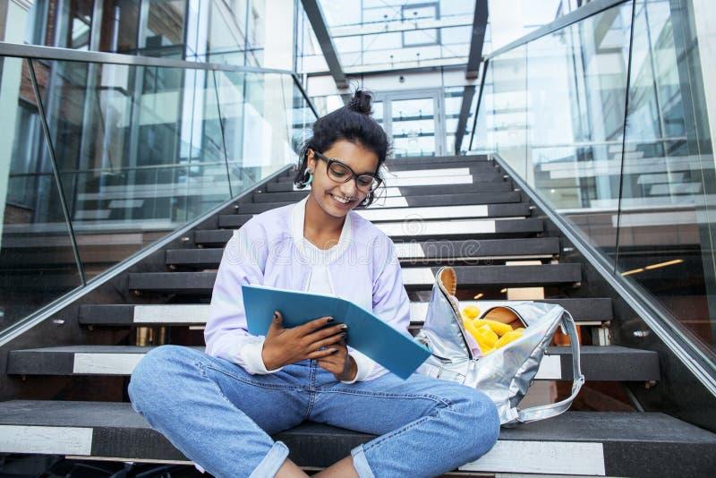 Muchacha india linda joven en el edificio de la universidad que se sienta en las escaleras que lee un libro, vidrios del inconfor fotos de archivo