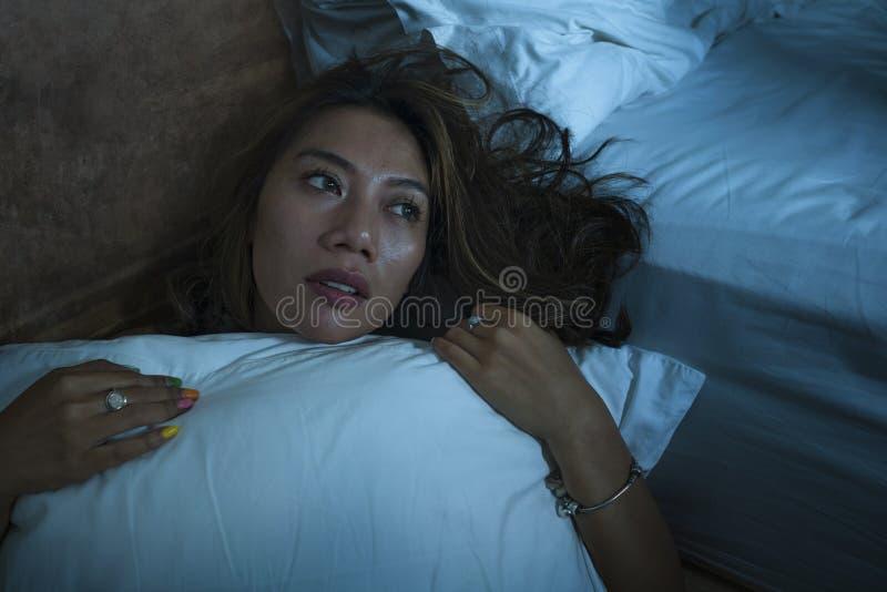 Muchacha indonesia asiática triste y deprimida hermosa joven en camisón en piso del dormitorio por el sufrimiento quebrado y perd foto de archivo libre de regalías