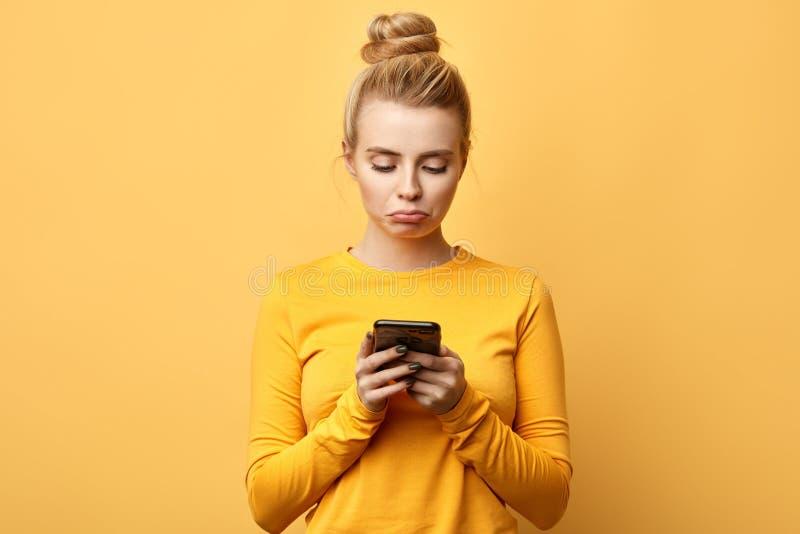 Muchacha infeliz decepcionada trastornada que lleva a cabo el mensaje de la lectura del teléfono móvil foto de archivo