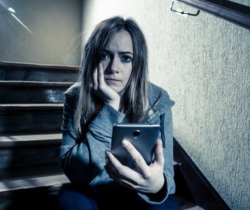 Muchacha infeliz deprimida triste del adolescente que sufre de cyberbullying por el teléfono elegante móvil que se sienta solamen imagenes de archivo