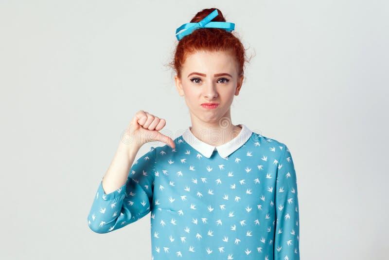 Muchacha infeliz hermosa joven con el vestido azul que muestra el pulgar abajo imagen de archivo