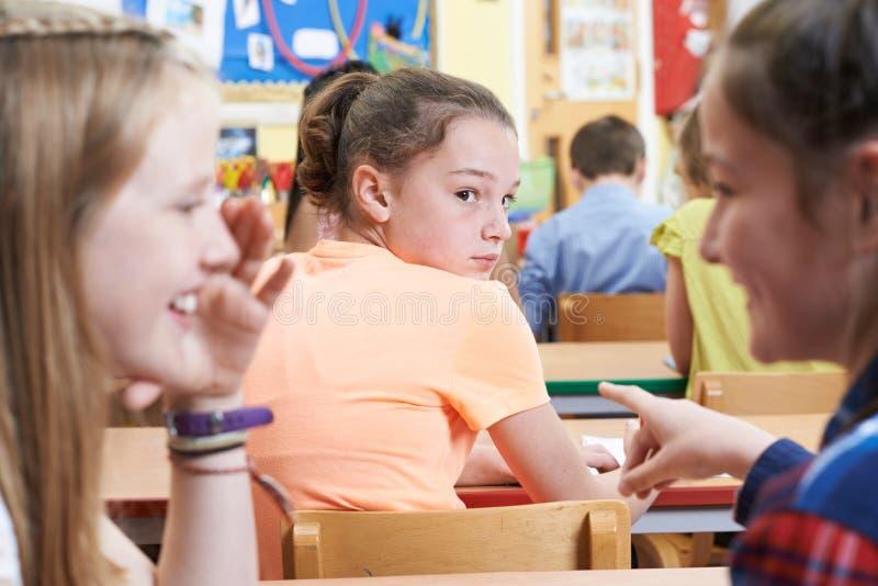 Muchacha infeliz que es cotilleada alrededor por los amigos de la escuela en sala de clase imágenes de archivo libres de regalías