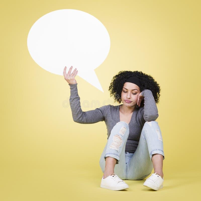 Muchacha infeliz que sostiene un globo de discurso blanco con el copyspace imagenes de archivo