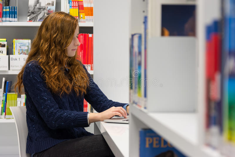 Muchacha inteligente hermosa de la universidad que usa el ordenador portátil en el modo blanco fotografía de archivo libre de regalías
