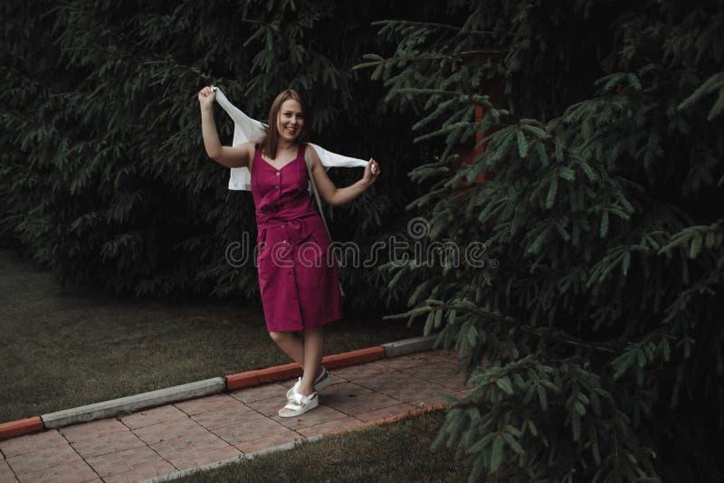 Muchacha interesante elegante en un vestido de Borgo?a contra una cerca de madera y un seto grueso de abetos Tener la diversi?n y imagenes de archivo