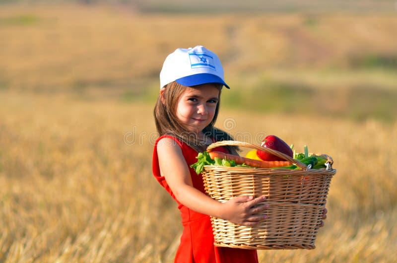 Muchacha israelí judía con la cesta de fruta en el día de fiesta judío de Shavuot fotografía de archivo