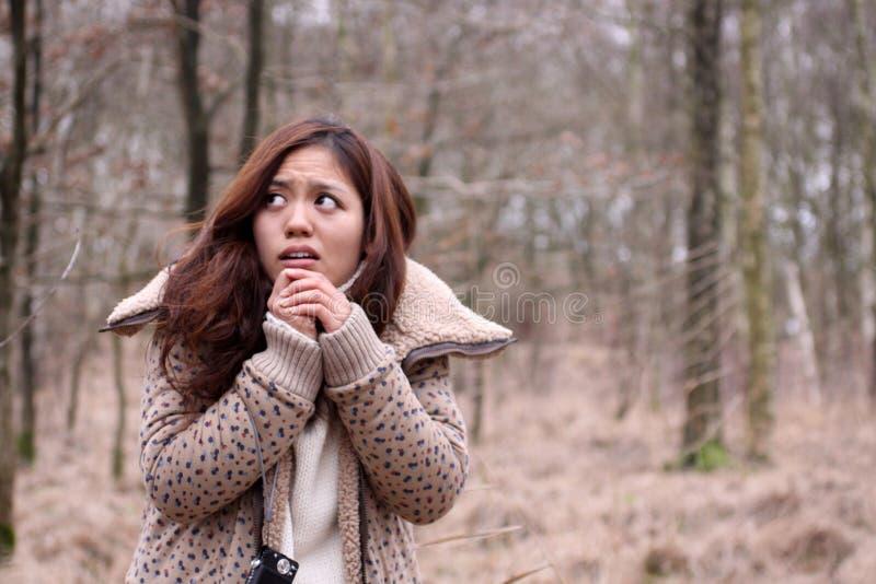 Muchacha japonesa asustada con la cámara en un bosque oscuro imagenes de archivo