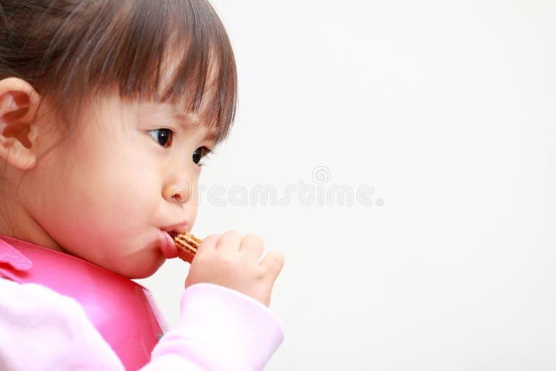 Muchacha japonesa que come las obleas fotografía de archivo libre de regalías