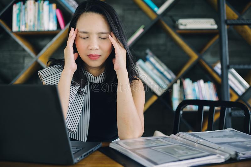 Muchacha joven asiática del negocio del retrato que trabaja el sufrimiento trabajado demasiado del dolor de cabeza fotografía de archivo libre de regalías