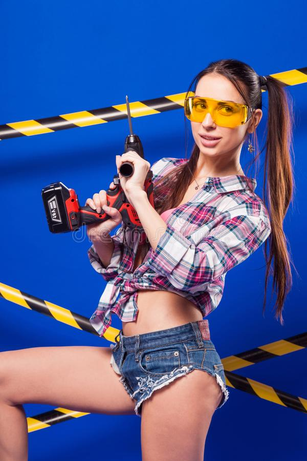 Muchacha joven atractiva del constructor en camisa, pantalones cortos del dril de algodón y gla chechered imagen de archivo libre de regalías