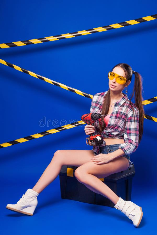 Muchacha joven atractiva del constructor en camisa, pantalones cortos del dril de algodón y gla chechered fotos de archivo