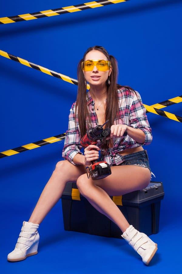 Muchacha joven atractiva del constructor en camisa, pantalones cortos del dril de algodón y gla chechered fotografía de archivo libre de regalías
