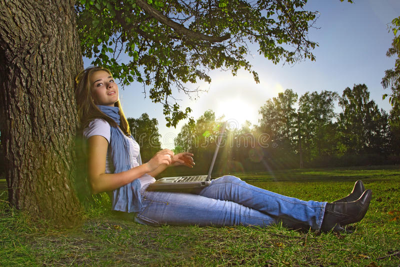 Muchacha joven de la belleza con la computadora portátil en parque imagen de archivo libre de regalías
