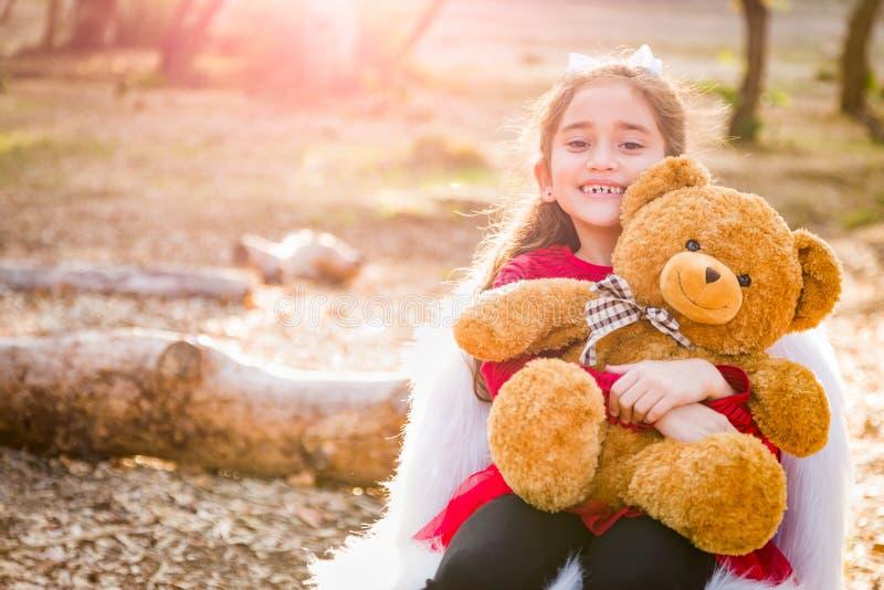 Muchacha joven de la raza mixta que abraza a Teddy Bear Outdoors foto de archivo libre de regalías