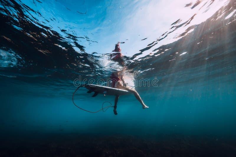 Muchacha joven de la resaca en el submarino de la tabla hawaiana en el mar imagen de archivo