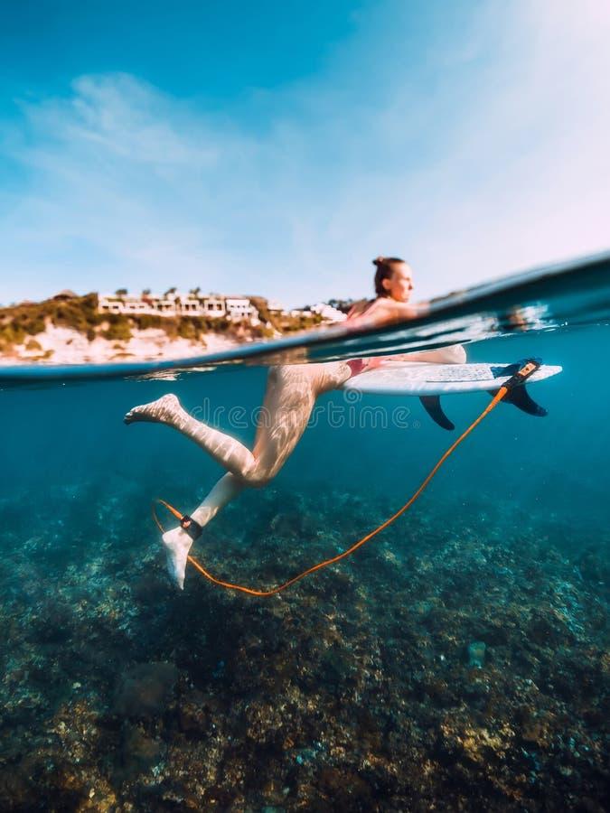 Muchacha joven de la resaca en el submarino de la tabla hawaiana en el mar fotografía de archivo libre de regalías
