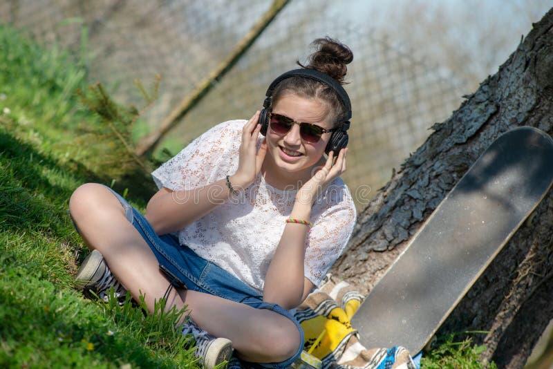 Muchacha joven del adolescente con la música que escucha de las gafas de sol al aire libre imagen de archivo