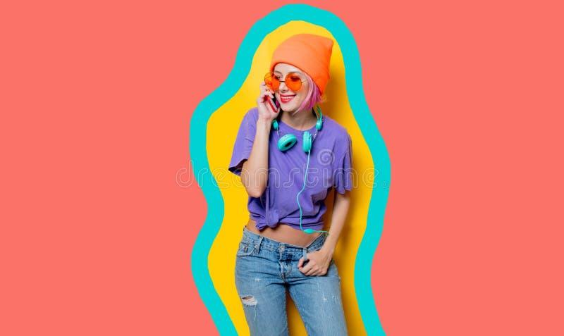 Muchacha joven del estilo con los auriculares en fondo coralino vivo exhausto del color fotos de archivo