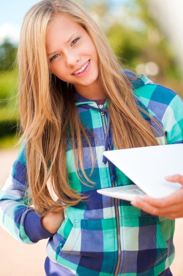 Muchacha joven del estudiante con la computadora portátil fotografía de archivo