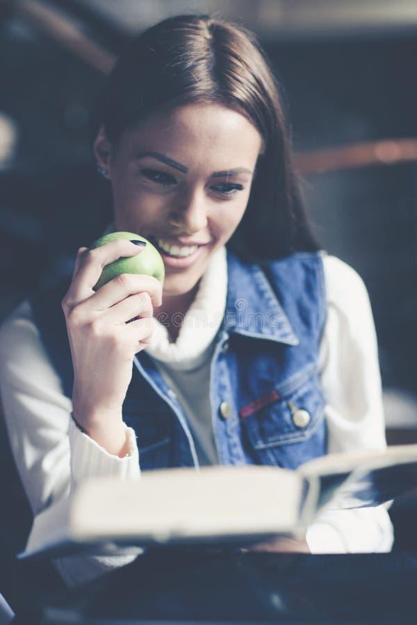 Muchacha joven del estudiante en casa que aprende y que come la manzana imágenes de archivo libres de regalías