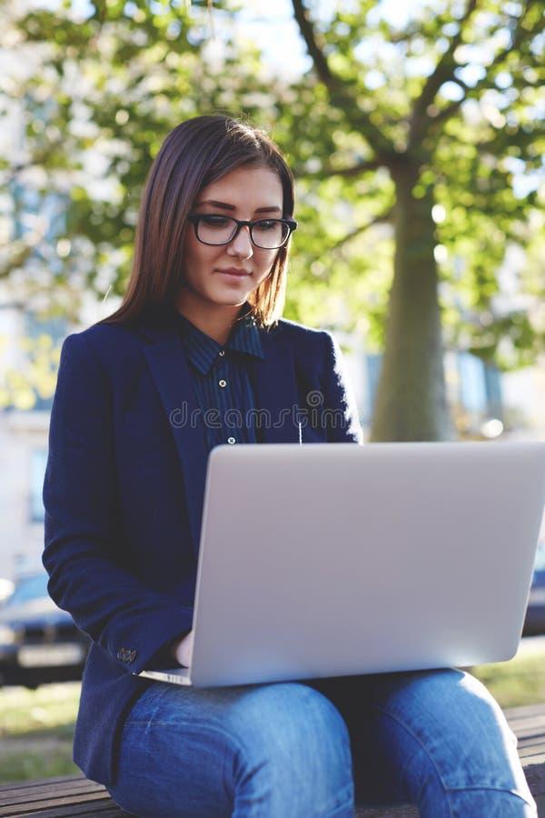 Muchacha joven del estudiante en los vidrios que se sientan en el banco del campus mientras que artilugio del ordenador portátil  imagen de archivo