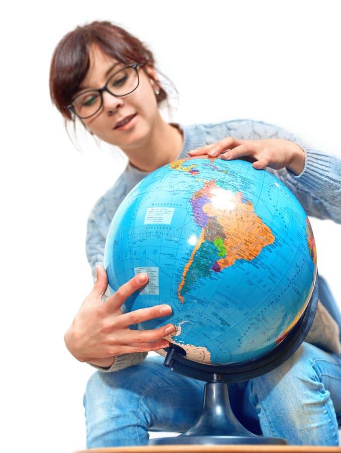 Muchacha joven del estudiante en vidrios que estudia la geografía con el globo fotos de archivo