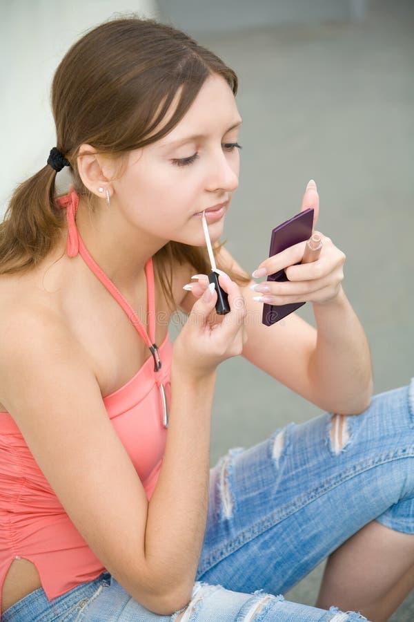 Muchacha joven del estudiante que aplica maquillaje fotos de archivo libres de regalías