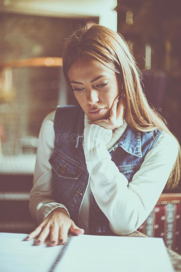 Muchacha joven del estudiante que lee y que estudia en casa fotos de archivo