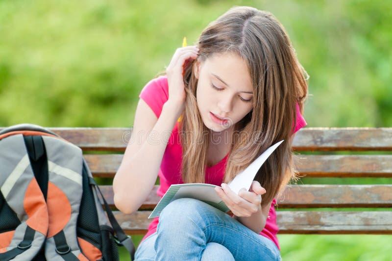 Muchacha joven del estudiante que se sienta en banco imágenes de archivo libres de regalías