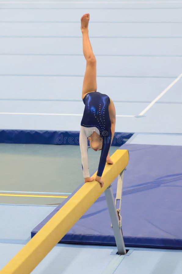 Muchacha joven del gimnasta que realiza rutina en haz de balanza imagen de archivo