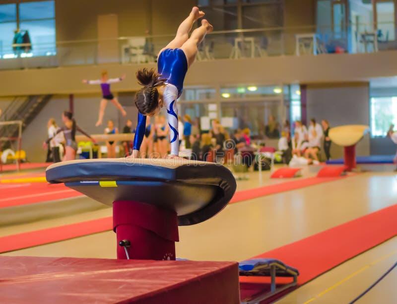 Muchacha joven del gimnasta que realiza salto imagenes de archivo