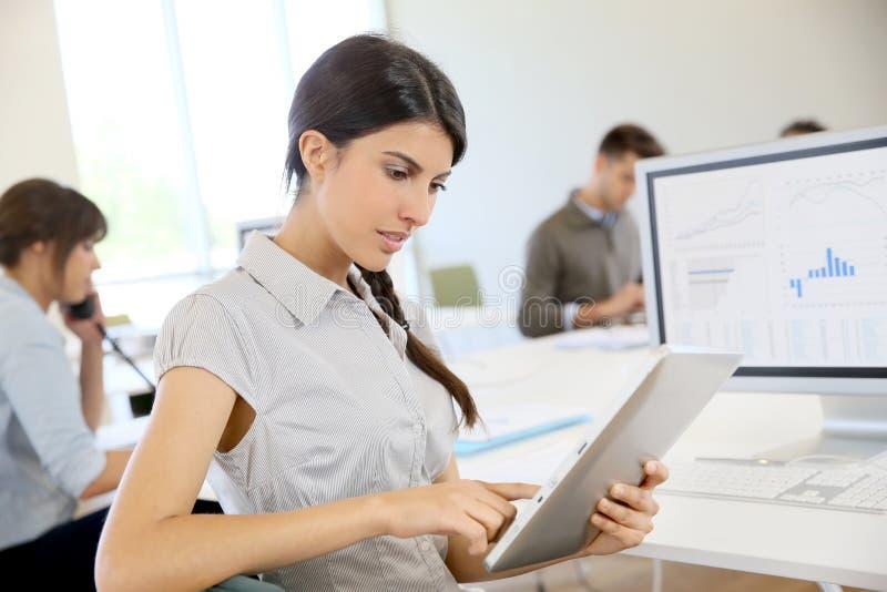 Muchacha joven del negocio que trabaja en la tableta, colegas por otra parte fotografía de archivo libre de regalías