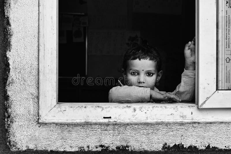 Muchacha joven del Nepali que mira hacia fuera una ventana de la escuela foto de archivo libre de regalías