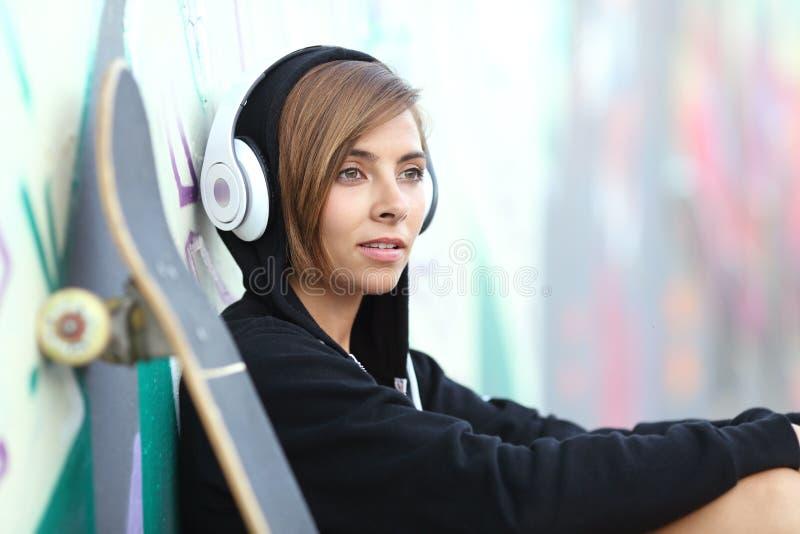 Muchacha joven del patinador que escucha la música con los auriculares fotografía de archivo