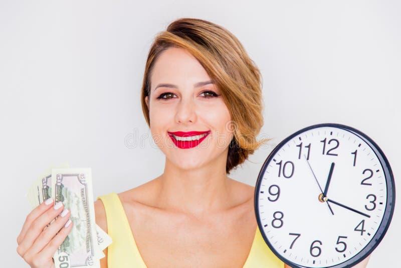 Muchacha joven del pelirrojo con el reloj y el dinero grandes imagen de archivo