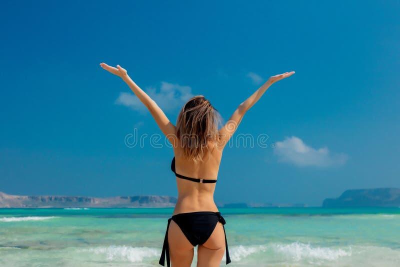 Muchacha joven del pelirrojo en bikini negro en la playa de Balos imágenes de archivo libres de regalías