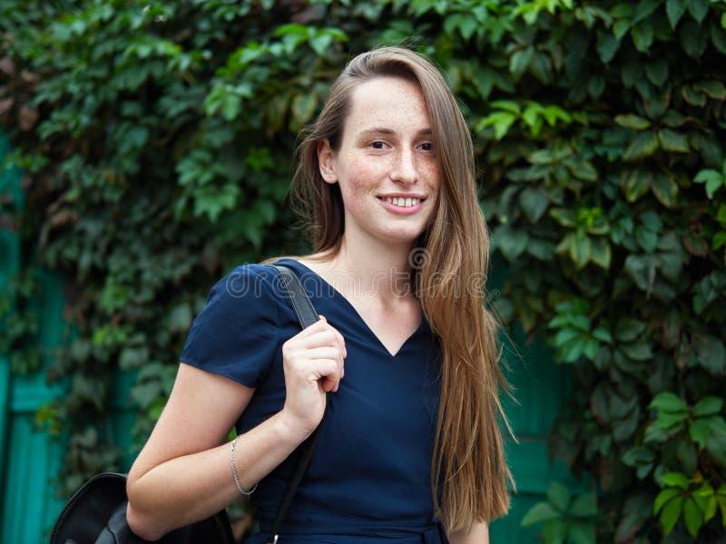 Muchacha joven del pelirrojo del inconformista con las pecas que llevan el vestido azul y la mochila negra que presentan contra l fotografía de archivo