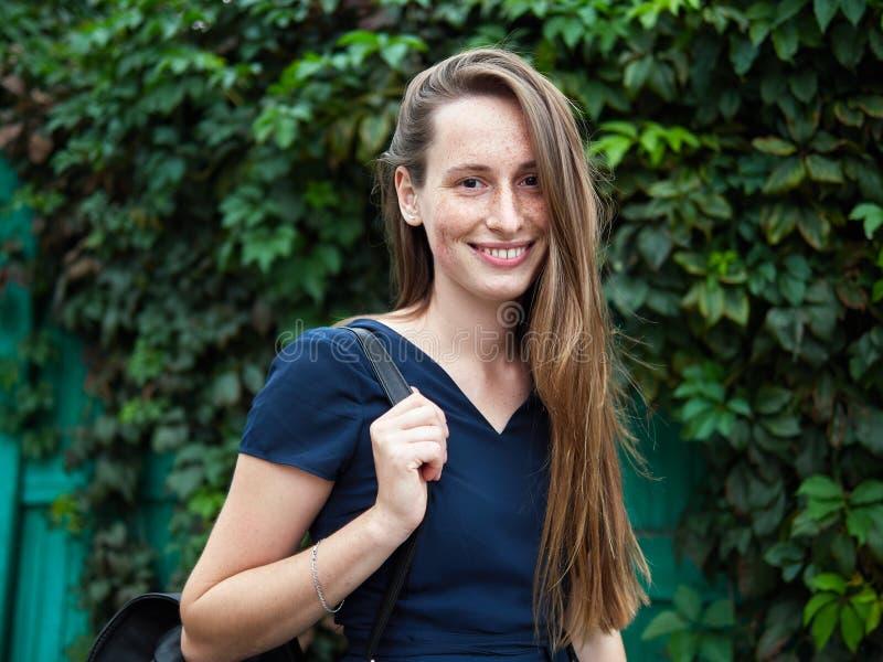 Muchacha joven del pelirrojo del inconformista con las pecas que llevan el vestido azul y la mochila negra que presentan contra l fotografía de archivo libre de regalías