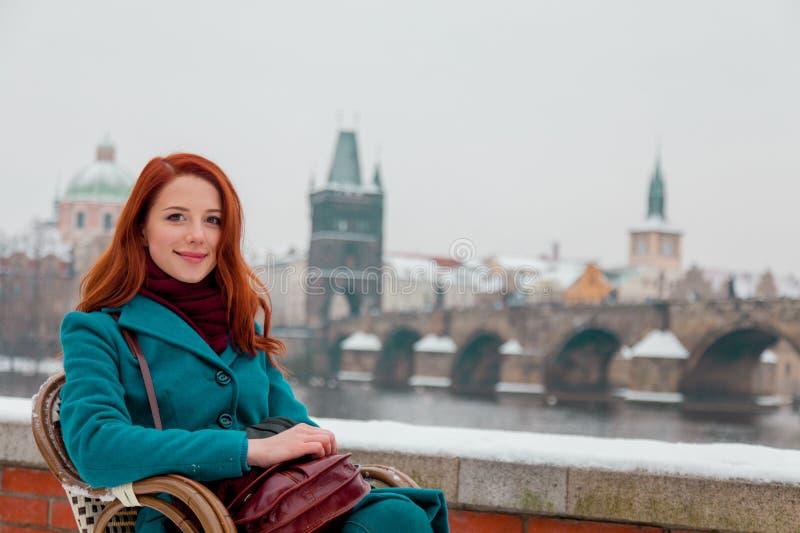Muchacha joven del pelirrojo que se sienta en silla con la ciudad vieja de Praga de la ciudad imágenes de archivo libres de regalías