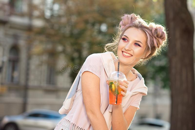 Muchacha joven feliz de la sonrisa en una camiseta rosada y una camiseta con un bollo brillante del maquillaje y del pelo que se  imagen de archivo libre de regalías