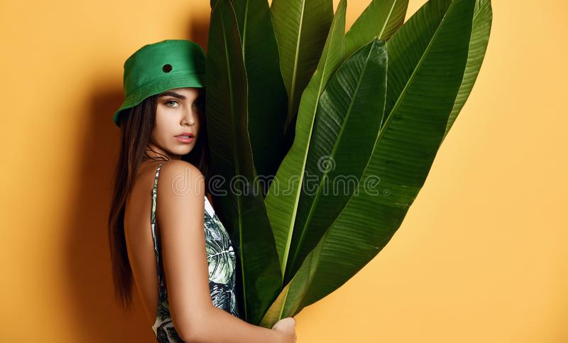 Muchacha joven hermosa de la moda con la piel perfecta en hoja tropical del plátano del control verde del sombrero en manos y cub fotografía de archivo