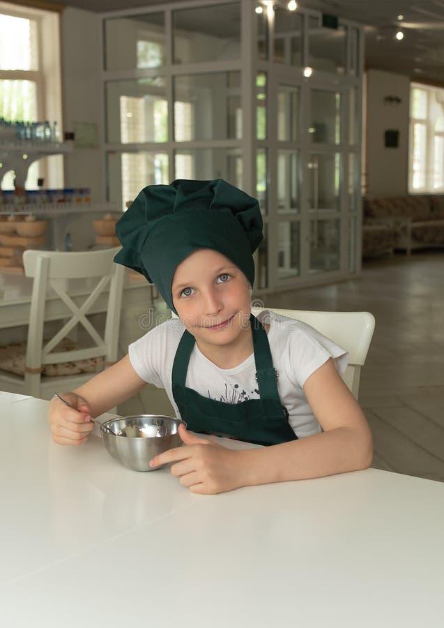 Muchacha joven hermosa del cocinero del cocinero en casquillo verde del cocinero con una cuchara y un cuenco foto de archivo libre de regalías