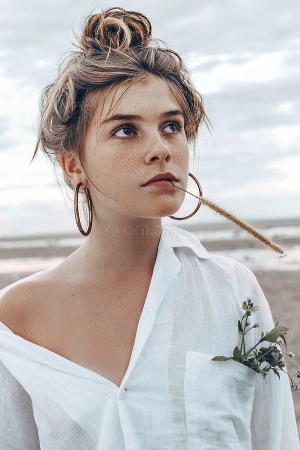 Muchacha joven hermosa del estilo del boho en la playa en la puesta del sol na joven fotografía de archivo