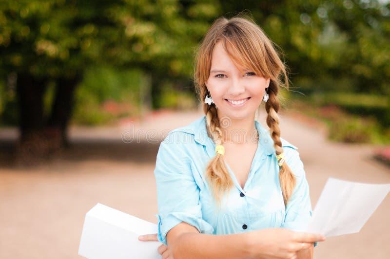 Muchacha joven hermosa del estudiante con la carta foto de archivo