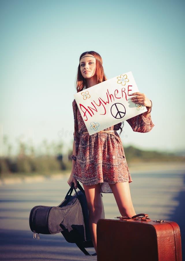 Muchacha joven hermosa del hippie que hace autostop en un camino imagenes de archivo